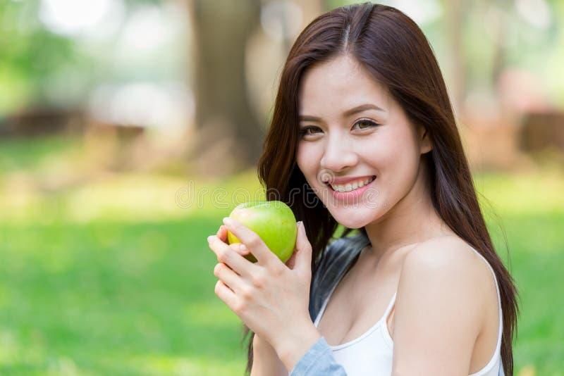 美丽的亚裔妇女式样手举行绿色苹果计算机营养果子 库存照片