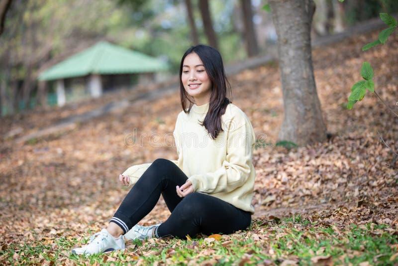 美丽的亚裔妇女微笑的愉快的女孩和佩带的衣服暖和冬天和在室外的秋天画象在公园 免版税库存照片