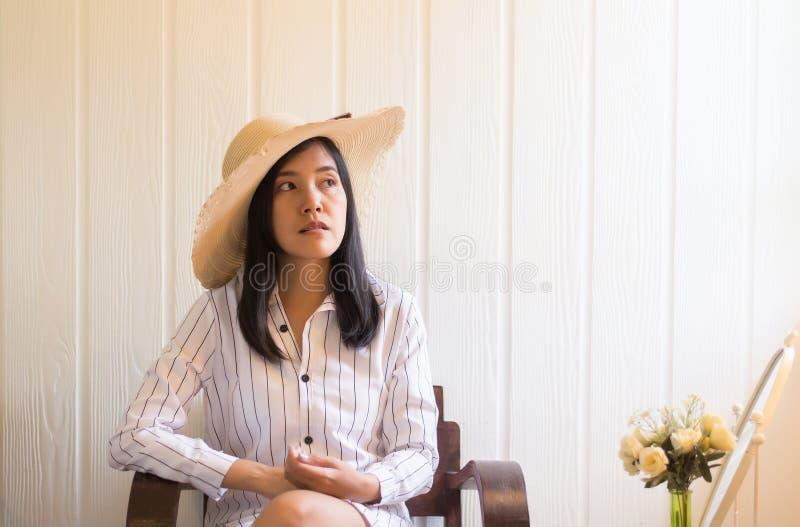 美丽的亚裔妇女画象放松和在家坐在窗口附近,正面认为,好态度 库存图片