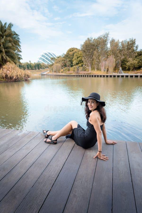 美丽的亚裔妇女画象时尚黑礼服的有她的在庭院的帽子的由海湾、秀丽和时尚概念 免版税库存图片