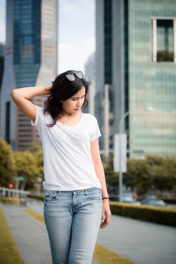 美丽的亚裔妇女画象白色T恤和牛仔裤的在新加坡市都市街道上  秀丽和时尚概念 免版税库存图片