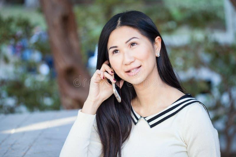 美丽的亚裔妇女谈话在有微笑的电话在她的f 库存照片
