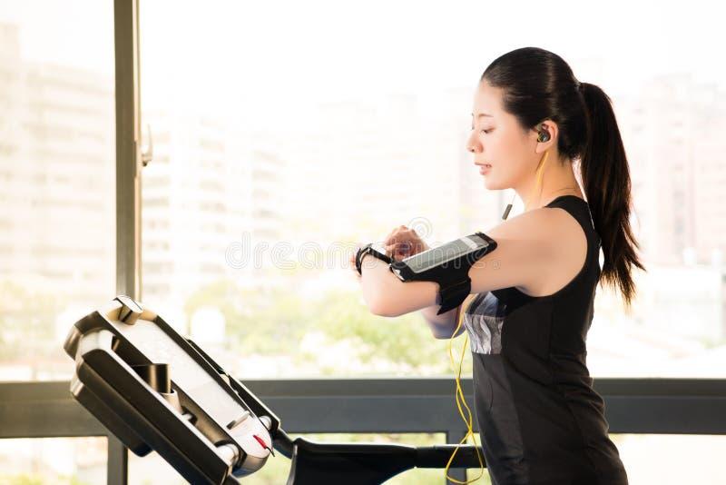 美丽的亚裔妇女连续踏车用途smartwatch听 免版税库存图片
