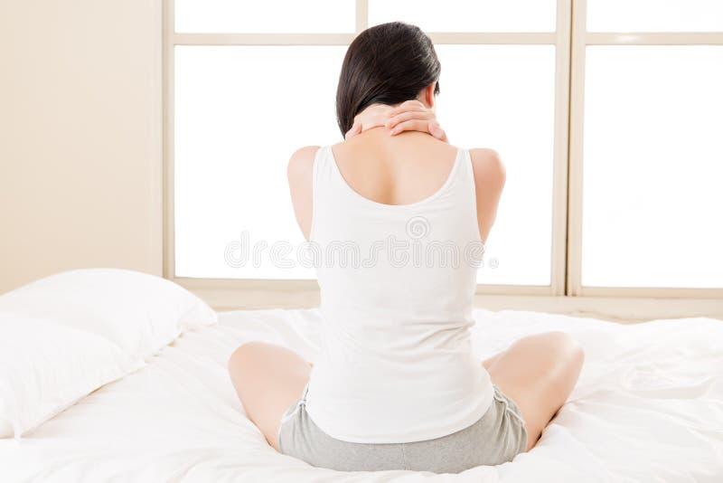 美丽的亚裔妇女遭受的脖子疼痛痛苦疲倦了 免版税图库摄影
