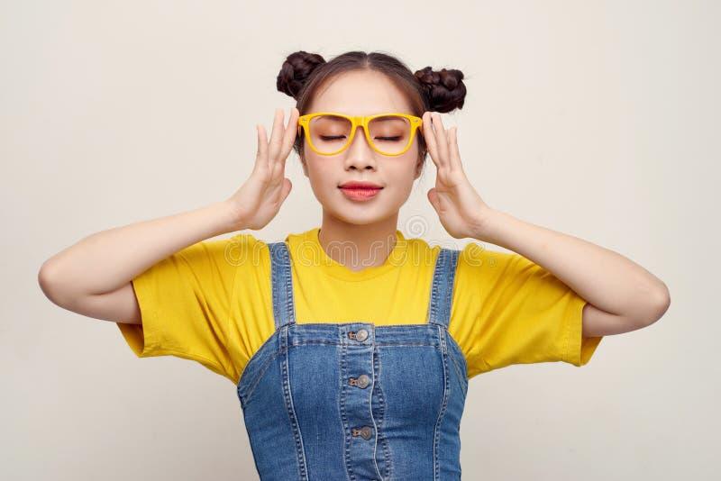 美丽的亚裔妇女食用穿牛仔裤粗蓝布工装和调整玻璃的头发两个小圆面包 库存图片