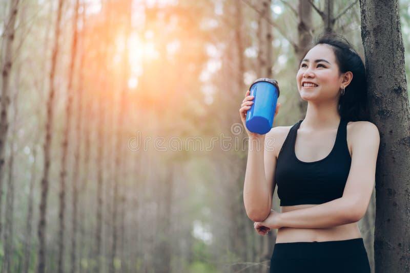 美丽的亚裔妇女饮用的蛋白质震动在森林里 免版税库存图片