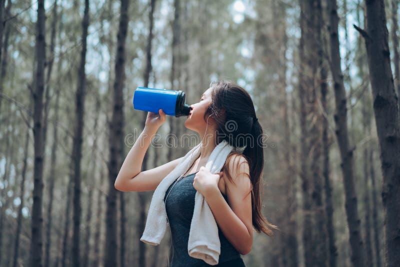 美丽的亚裔妇女饮用的蛋白质震动 免版税库存图片