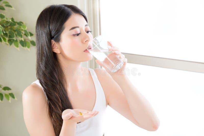 美丽的亚裔妇女饮用水吃营养补充 免版税图库摄影