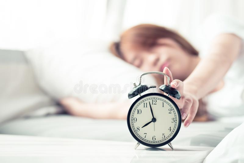 美丽的亚裔少妇在早晨关闭闹钟,为与闹钟的睡眠醒 免版税库存图片