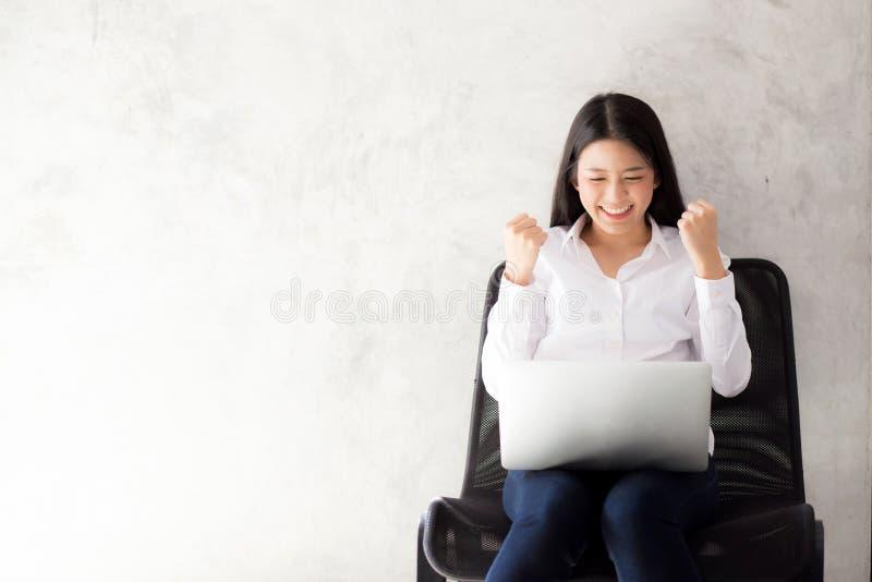 美丽的亚裔少妇激动和高兴与膝上型计算机的成功 免版税库存照片