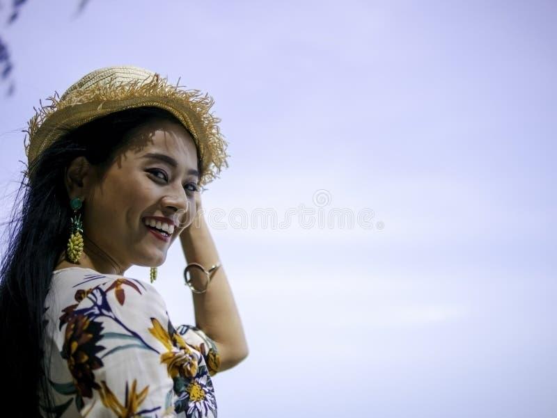 美丽的亚裔有旅行菠萝的耳环的妇女佩带的葡萄酒礼服海边 免版税库存照片