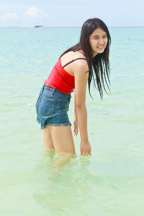 美丽的亚洲妇女戏剧水在海 库存照片
