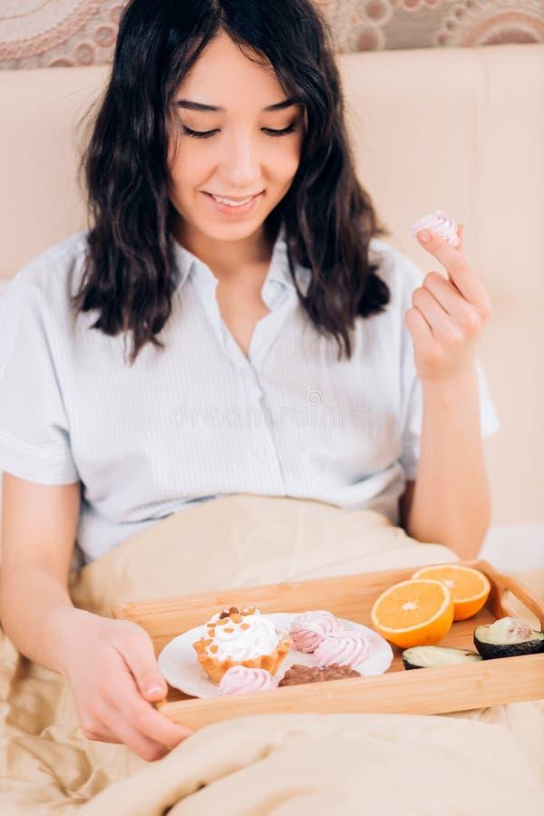 美丽的令人敬畏的深色头发的妇女吃鲜美早餐在床在她的舒适卧室 少女侧视图照片蓝色的 免版税库存照片