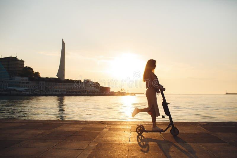 美丽的体育女孩在一个夏天公园乘坐滑行车在一好日子 免版税图库摄影