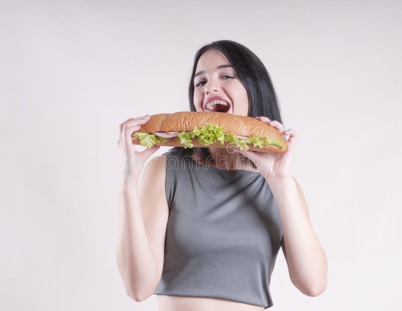 美丽的体育女孩深色的吃三明治亭亭玉立的午餐演播室愉快节食 库存图片