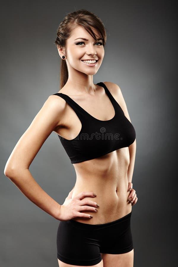 美丽的体育妇女用在臀部的手 免版税库存图片
