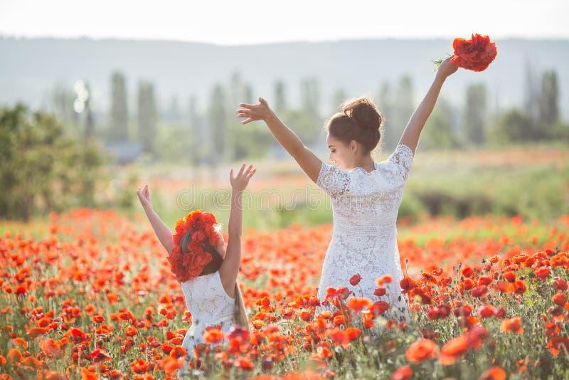 美丽的使用在春天花田的母亲和她的女儿 免版税图库摄影