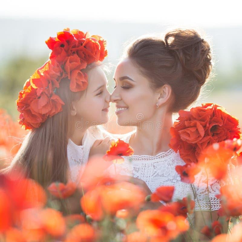 美丽的使用在春天花田的母亲和她的女儿 免版税库存照片
