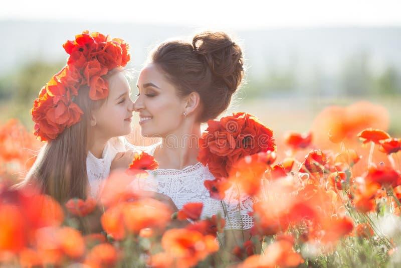 美丽的使用在春天花田的母亲和她的女儿 免版税库存图片