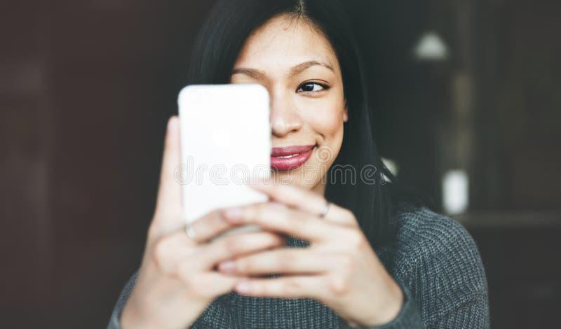 美丽的使用智能手机概念的妇女使变冷的生活方式 免版税库存图片