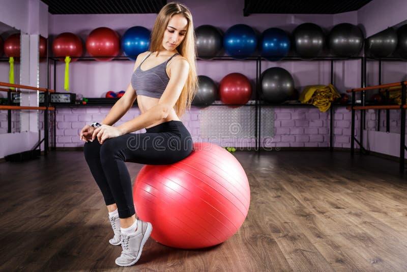 年轻美丽的健身女孩坐红色球 免版税库存照片