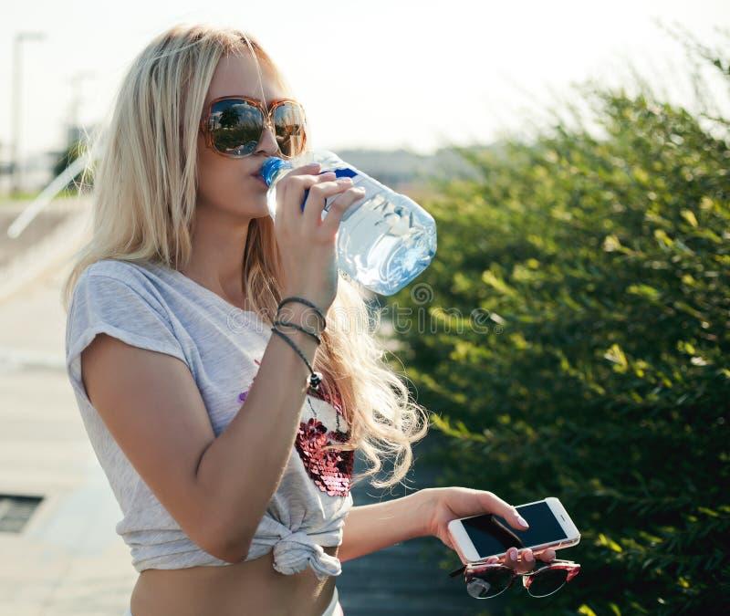 美丽的健身运动员白肤金发的少妇饮用水以后在日落在海滩室外por的晚上夏天制定出行使 库存图片