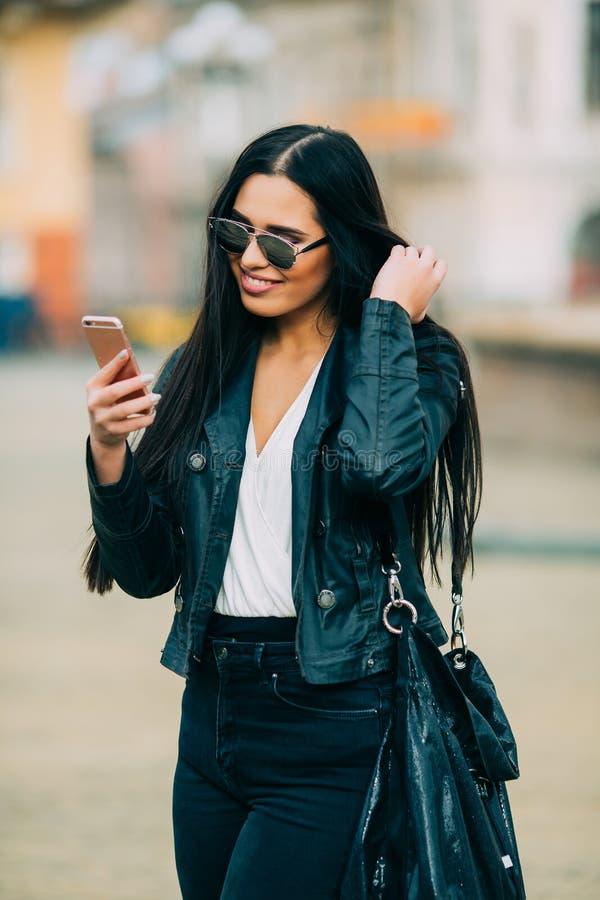 年轻美丽的偶然女孩采取在她的手机的一selfie有太阳镜的 库存照片