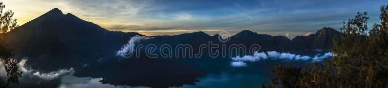 美丽的全景在湖边的射击高岩石小山与云彩和令人惊讶的日出 库存图片