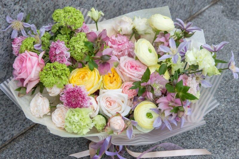 美丽的典雅的卖花人设计师白色黄色桃红色婚姻的花束有玫瑰特写镜头的 免版税库存照片