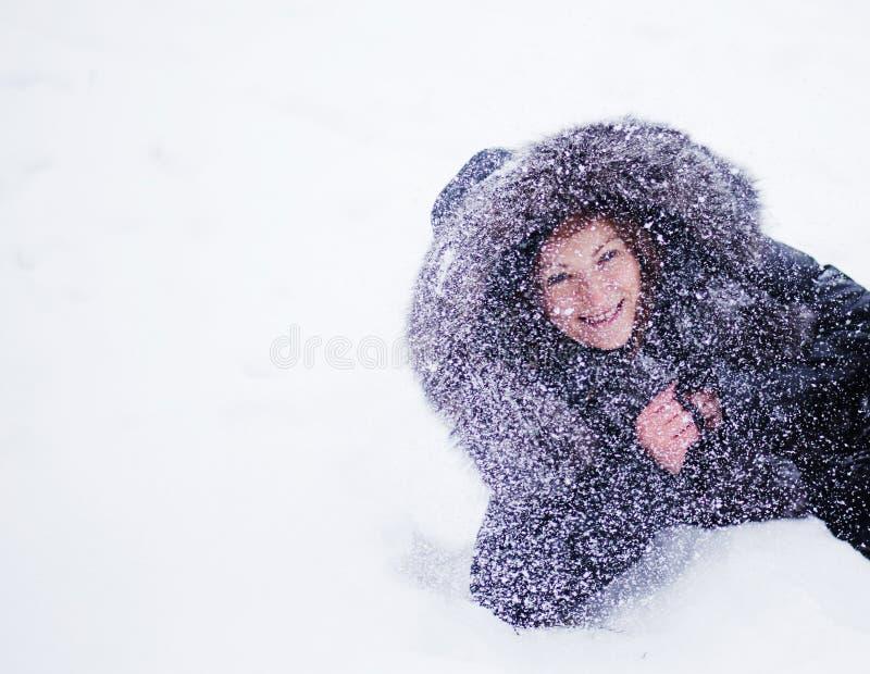 美丽的冬天妇女获得乐趣在说谎在雪的冬天公园 ba 库存照片