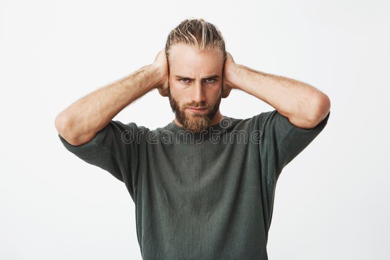 美丽的北欧有胡子的人闭合值的耳朵画象用显示朋友他的手穿上` t要听见他的借口为 库存图片