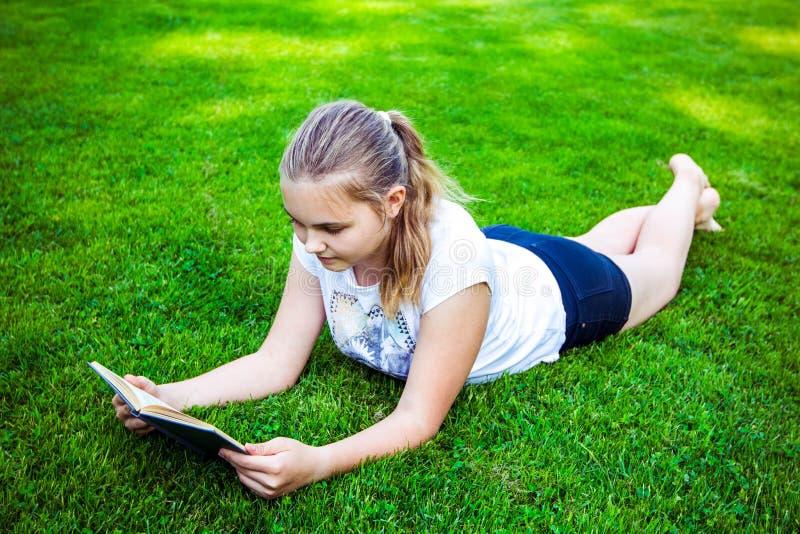 美丽的十几岁的女孩在绿草在夏天好日子说谎并且读书在公园 免版税库存图片