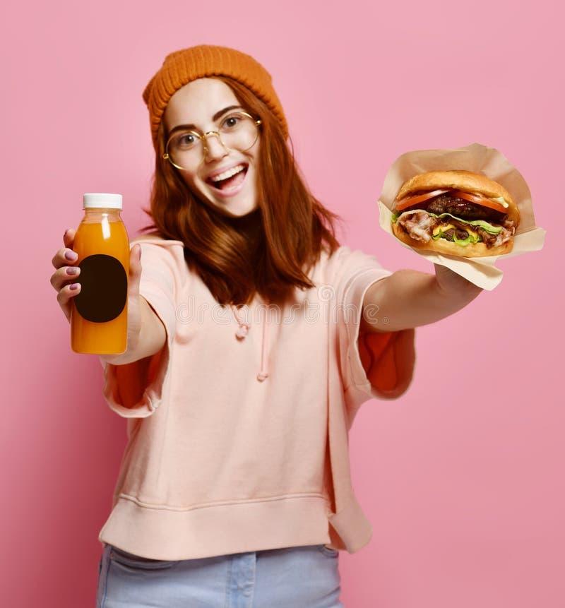美丽的十几岁的女孩用红色头发和帽子藏品汉堡和饮料在两只手中 库存图片