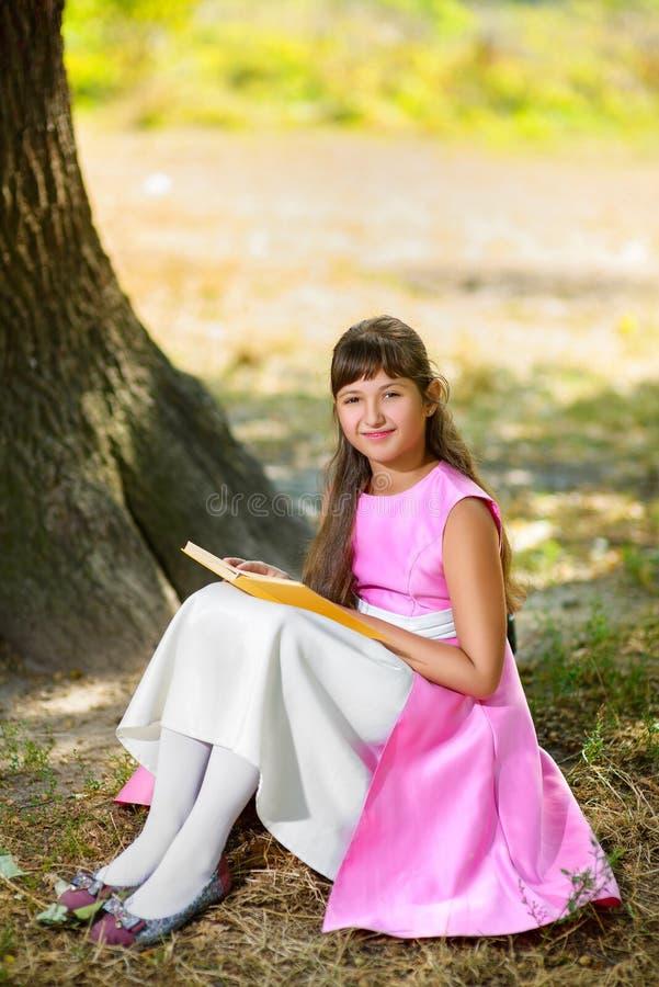 美丽的十几岁的女孩读书在巨大下 免版税库存图片