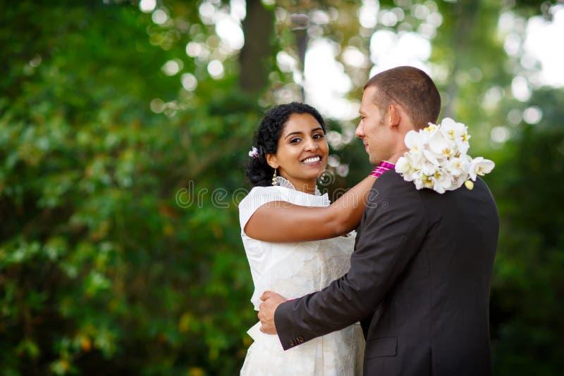 美丽的印地安新娘和白种人新郎,在夏天公园 开花愉快的藏品妇女年轻人 微笑年轻的人,夫妇 免版税库存照片