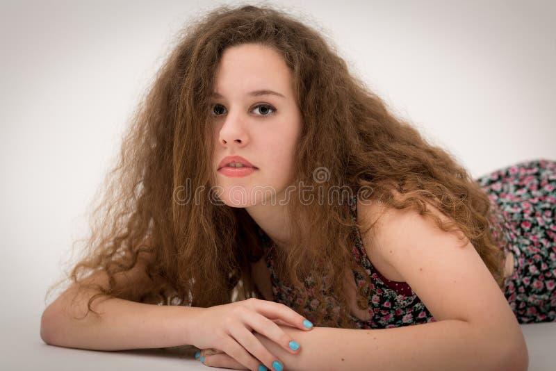 美丽的卷曲在地板上的姜女孩十几岁的女孩 库存照片