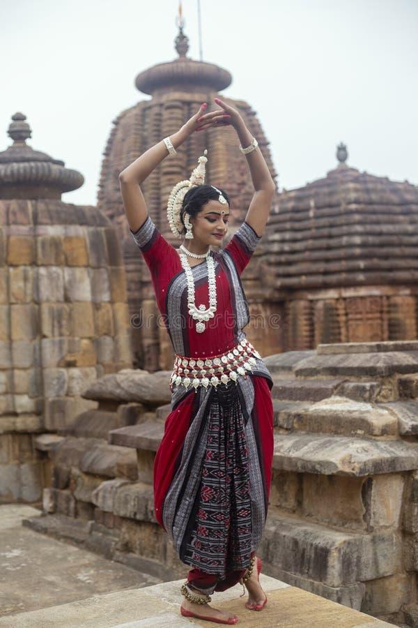 美丽的反对Mukteshvara寺庙背景的Odissi舞蹈家触击的姿势有雕塑的在布巴内斯瓦尔,Odisha,印度 免版税库存照片