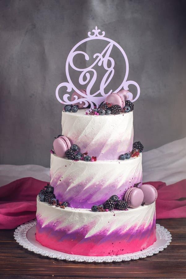 美丽的可口三层婚宴喜饼装饰用在桃红色紫色颜色的莓果蓝莓和黑莓 库存照片