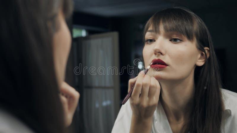 美丽的可爱的妇女组成她自己在镜子前面准备好photoshot和闪光她的眼睛到照相机 免版税库存照片