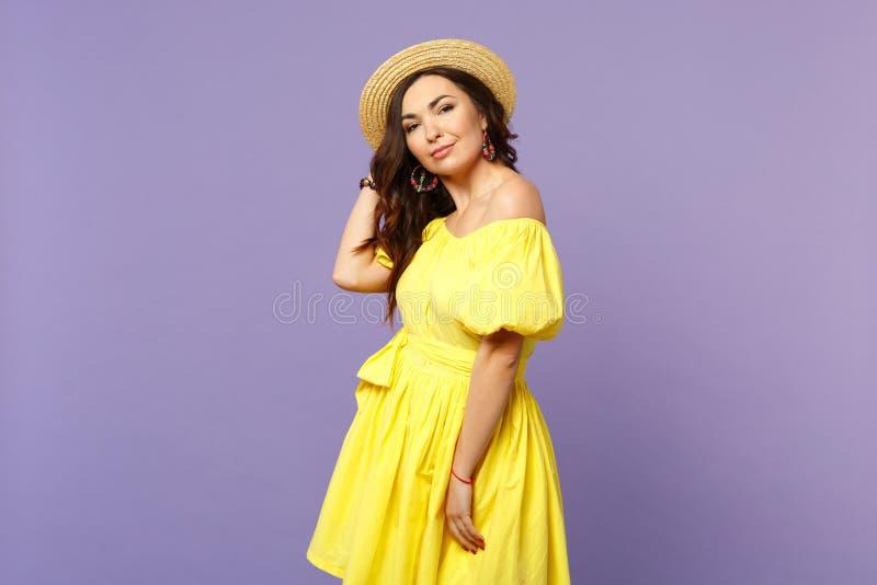 美丽的可爱的年轻女人画象黄色礼服的,看照相机的夏天帽子隔绝在淡色紫罗兰 库存照片