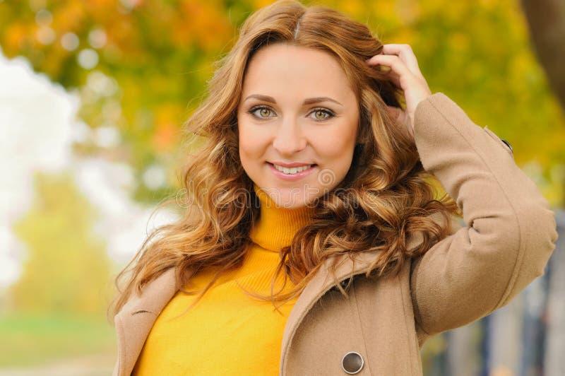 美丽的可爱的微笑的少妇画象在秋天p 库存图片