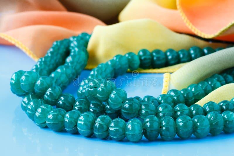 美丽的可贵的鲜绿色石小珠在蓝绿色backgrou 库存图片