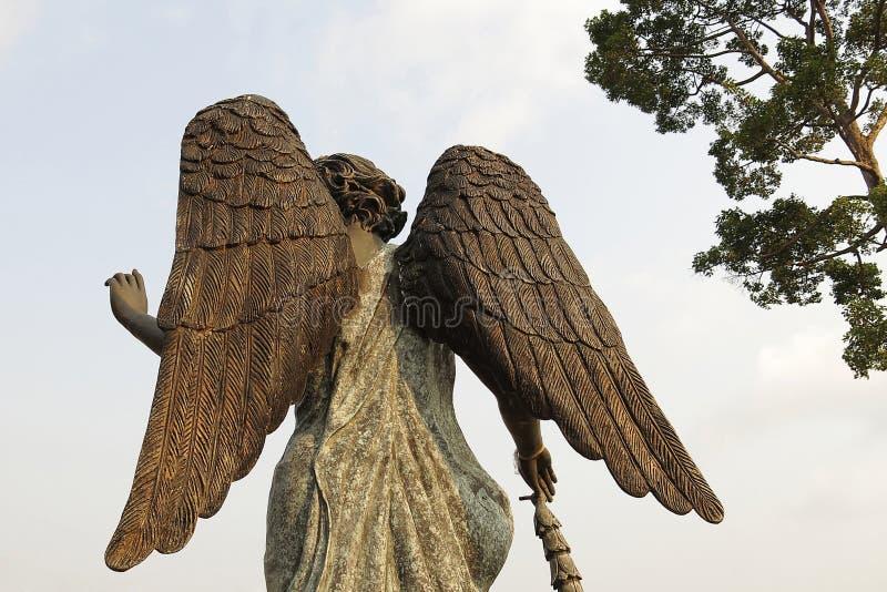 美丽的后侧方天使雕象在日落前的阳光下 免版税库存照片