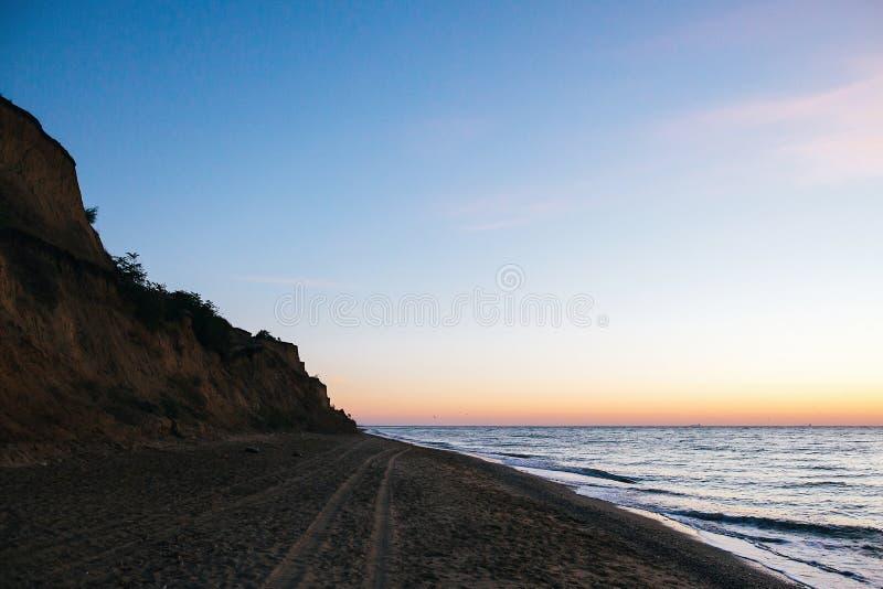 美丽的含沙峭壁和桃红色天空与太阳上升在海波浪上在热带海岛上 波浪在日落光的海洋 平静的安静 免版税库存照片
