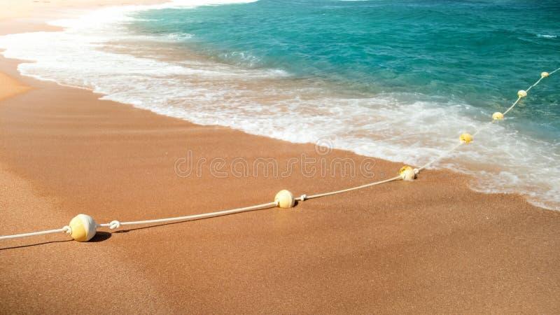 美丽的含沙海海滩特写镜头滚动在救生圈的照片和波浪在绳索排行 库存照片