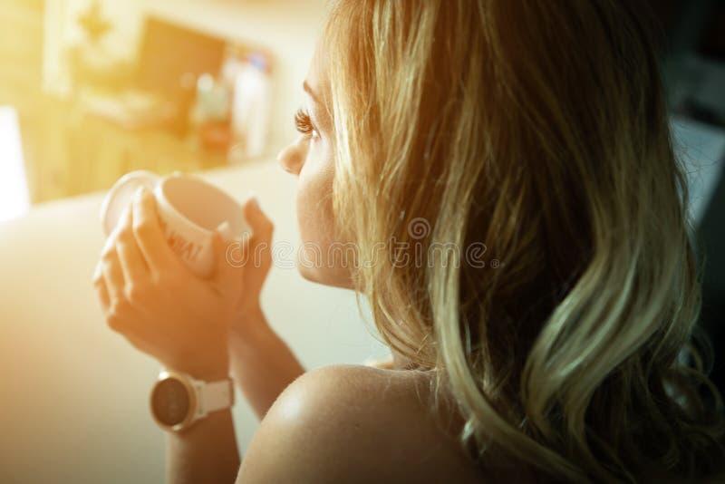 美丽的咖啡饮用的早晨妇女 免版税库存图片