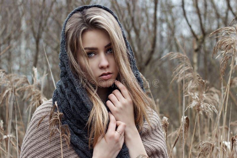 美丽的哀伤的女孩在领域走 在棕色口气的照片 免版税图库摄影
