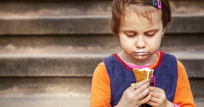 美丽的哀伤的小孩女孩onely吃冰淇淋 免版税库存照片