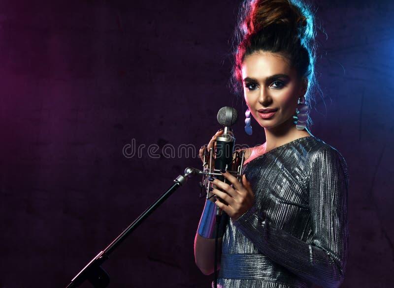 美丽的唱歌的女孩卷曲非洲的头发歌手唱歌与话筒在阶段的卡拉OK演唱歌曲在黑暗的霓虹灯 免版税库存照片