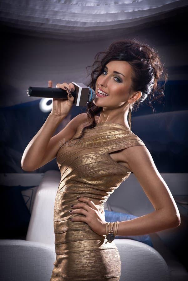美丽的唱歌的女孩 有话筒的秀丽妇女 魅力式样歌手 免版税库存图片